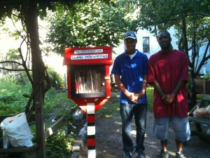 Rayquan Winchester and Christopher Dotson after planting and painting the Little Free Library in the Harlem Success Garden. They will plant two more in Marcus Garvey Park this spring.